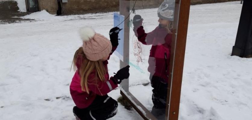 två barn som målar utomhus